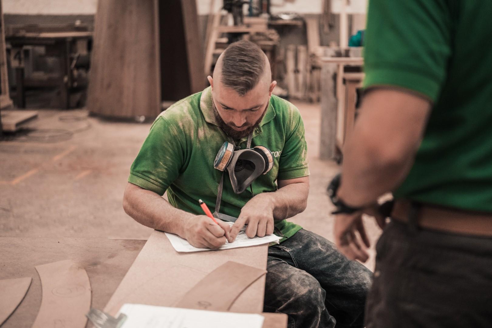 man-in-green-crew-neck-t-shirt-writing-on-white-paper-3637788.jpg